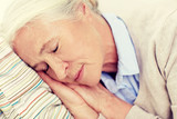 happy senior woman sleeping on pillow at home