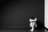 Sad woman sitting in the corner of a room, head on the knees, face is hidden, black and white