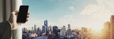 Hand holding mobile phone with panoramic cityscape of Bangkok city in sunrise, vintage tone
