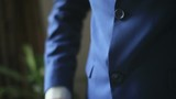 Young handsome man in stylish blue suit buttons up his blazer
