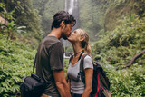 Fototapety Couple in love kissing near a waterfall in forest