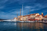 Sailboats and yachts moored to the quay port of Saint-Tropez, France.