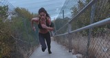 Outdoor shot of fit young woman running up stairs. Female athlete climbing up the steps.