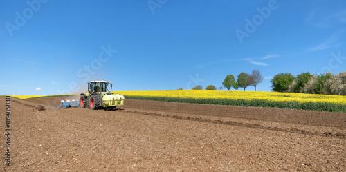 Poster Traktor auf einem Feld bei der Aussaat