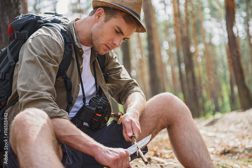 Skillful man whittling pole in forest Poster