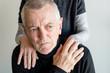 Distressed older man with short grey hair and black top being comforted by older woman (selective focus)