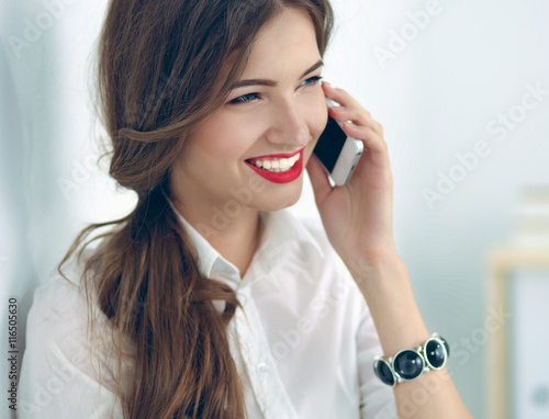 Poster Smiling businesswoman talking on the phone at the office