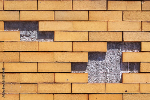 Yellow brick wall damaged background