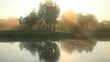 Rays of the sun in the morning mist. Beautiful landscape reflected in a river.