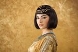 Beautiful Egyptian woman like Cleopatra on golden background - 116528279