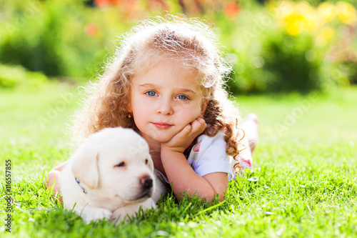 Poster Little girl with a labrador puppy, outdoor summer