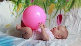 charming baby is lying in bed and plays with a big red ball