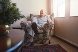 Elderly man sitting on arm chair at old age home