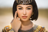 Beautiful woman with fashion make-up and hairstyle like Egyptian queen Cleopatra outdoors against desert - 116626046