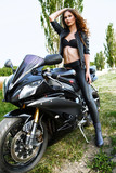 Sexual biker woman wearing black leather jacket with her sport m