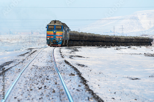 Poster Freight train moving on snow-covered tracks.
