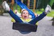 Cute child swings at kid park playground