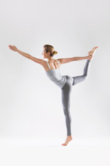 Beautiful young woman doing yoga on a gray studio background © milazvereva