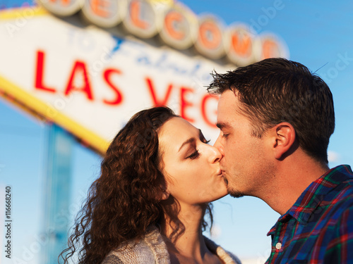 Poster couple having romantic kiss in front of the welcome to las vegas sign