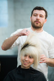 male hairdresser puts woman