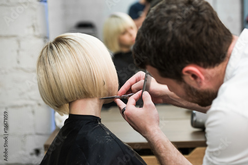 Plakát, Obraz Hairdresser cutting client's hair in salon with electric razor closeup