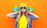 Fototapety Fashion pretty cool girl with skateboard over colorful orange ba