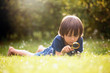 Beautiful happy child, boy, exploring nature with magnifying gla