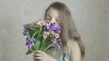 Beautiful happy girl enjoys bouquet flowers of irises and alstroemeria.