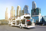 Fototapety The trailer transports  new cars on highway with big city background use for transportation industry or automotive industry