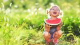 Fototapety Happy child girl eats watermelon