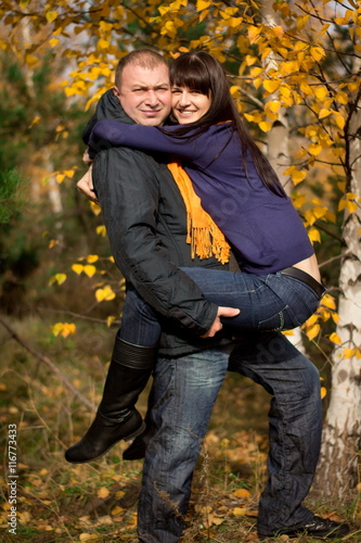 the man is holding his woman in autumn forest