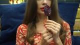 Long hair girl holding red spiral lolly