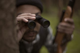 Interracial hunter in the forest looking through binocular
