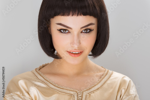 Aluminium Smiling girl with Cleopatra's make-up and haircut posing in studio