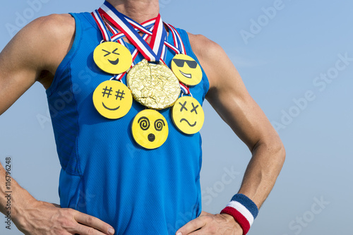 Athlete wearing gold medals with bright yellow emoji faces standing in front of Poster