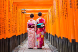 Fototapety Two geishas among red wooden Tori Gate at Fushimi Inari Shrine in Kyoto, Japan. Selective focus on women wearing traditional japanese kimono.