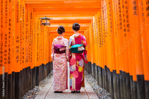 Fotobehang Kyoto Two geishas among red wooden Tori Gate at Fushimi Inari Shrine in Kyoto, Japan. Selective focus on women wearing traditional japanese kimono.