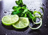 Green limes with mint and water drops on black background