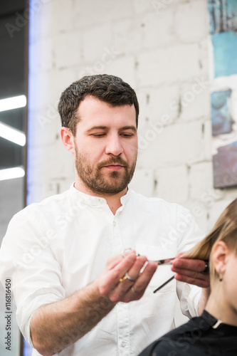 Male hairdresser making haircut for a client in professional hairdressing salon Poster