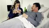 Woman putting needle to boyfriend in hospital.