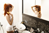 Attractive red-haired woman brushing hair