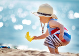 Fototapety little boy playing at the beach in straw hat
