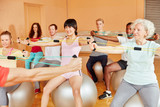 Gruppe mit Seniorin bei Kurs im Fitnesscenter