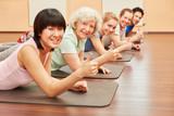 Gruppe im Yoga Kurs hält Daumen hoch