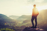 Traveler young man standing in summer mountains at sunset and enjoying view of nature - 116856097
