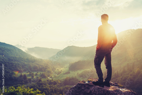 Traveler young man standing in summer mountains at sunset and enjoying view of n Poster