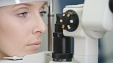 Closeup of beautiful young woman having her eyes examined with biomicroscopic slit lamp device during comprehensive eye exam