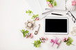 Workplace with tablet, pen, notebook, flowers and eyeglasses. Flat lay composition. Top view