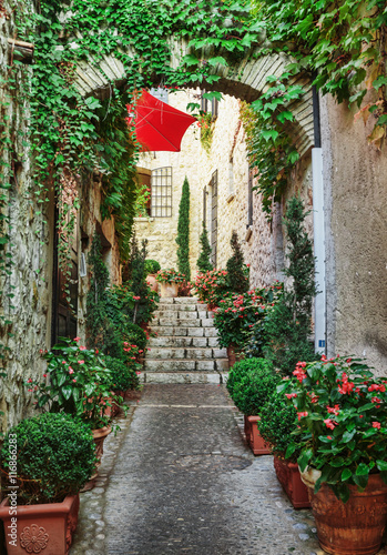 Fototapety, obrazy : Narrow street with flowers in the old town  in France.