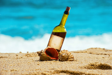 Alcohol wine bottle in the sand on a tropical beach